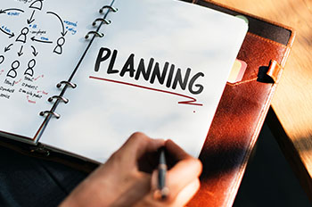 Woman writing in a planner with the word 'planning' visible